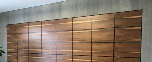 Maßangefertigte Möbel . Schrank mit Nußbaumfronten mit Betonplatten eingerahmt